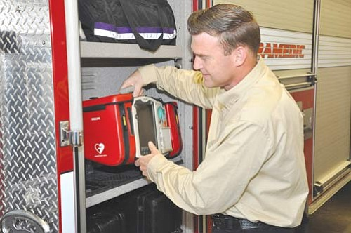 BUTCH MERIWETHER/Courtesy<BR><BR> Daniel Barlow loads up paramedic equipment onto a Kingman Fire truck. Barlow, one of 10 EMTs currently undergoing the field practical application portion of paramedic training in Kingman, has been associated with fire departments since the early '90s.