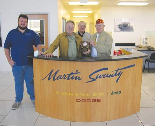 """JAMES CHILTON/Miner<br> Toys for Tots Coordinator and Marine Corps Reserve member Norman Burns (far right) presents a plaque to Cody and Martin Swanty of Swanty Chrysler Dodge Jeep, Monday expressing appreciation for them assisting the 2009 drive by donating the use of a showroom to serve as the charity's headquarters. Standing to the left of Burns is local Marine Corps Reserve Chaplain Jerry Ambrose.  <a href=""""http://kingmandailyminer.com/Formlayout.asp?formcall=userform&form=20"""">Click here to purchase this photo</a>"""