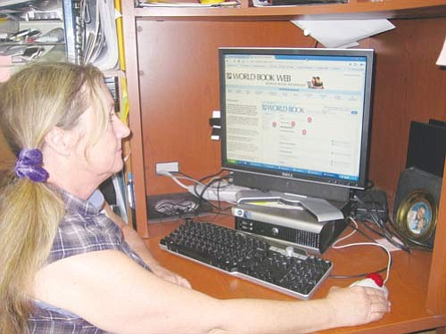 """ERIN TAYLOR/Miner<br> Kathy McGehee, marketing specialist for the Mohave County Library, logs onto the World Book Web Thursday from her office at the Kingman branch. <a href=""""http://kingmandailyminer.com/Formlayout.asp?formcall=userform&form=20"""">Click here to purchase this photo</a>"""