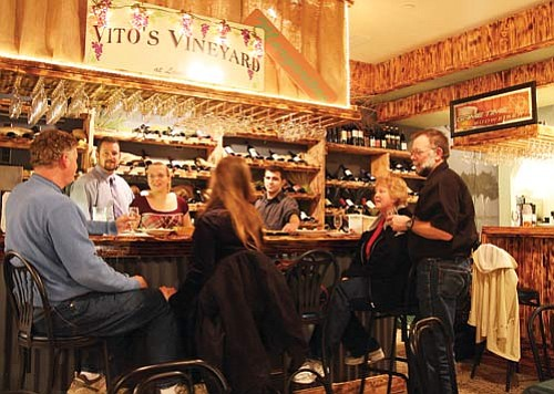 """JC AMBERLYN/Miner<br><br> Patrons enjoy Vito's Vineyard at Lombardo's on Friday night. Behind the bar, from left, are General Manager David Goodbar, Jennifer MacDonald from Young's Market and bartender Nick Lombardo, the owner's son.<br> <a href=""""http://kingmandailyminer.com/Formlayout.asp?formcall=userform&form=20"""">Click here to purchase this photo</a>"""