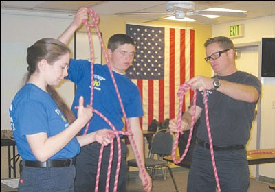 "ERIN TAYLOR/Miner Firefighter Dan Winder leads Kingman Fire Department Explorers Renill Esquerra (left) and Brian Abraham through a knot exercise during a recent meeting this month. <a href=""http://kingmandailyminer.com/Formlayout.asp?formcall=userform&form=20"">Click here to purchase this photo</a>"
