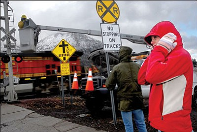 JENN IRELAND/Arizona Daily Sun<br> Kelly Simonson covers her ears as a train blows its horn while passing by the Fanning Street railroad crossing in Flagstaff in December 2007. During the test, people from around town gathered at the crossing or in their homes to listen to the comparison of wayside horns versus regular train horns that could reduce the amount of noise produced by trains passing through town.