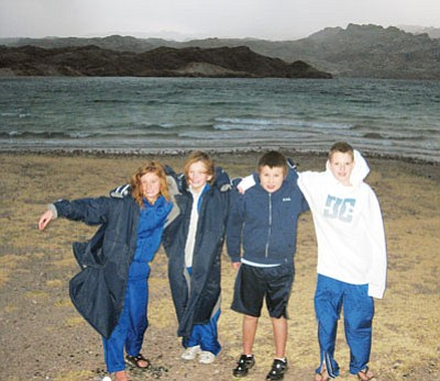 Courtesy<br> A cold day at Lake Mohave has, from left, Sophia Depner, Victoria Depner, Jacob Miyauchi and Kaden Weaver of the Kingman Dolphins ready for the Alcatraz Swim April 10.