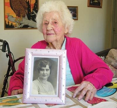 JAMES CHILTON/Miner<br /><br /><!-- 1upcrlf2 -->Bea Anderson, who celebrates her 100th birthday Wednesday, poses with a photograph of herself as a high school senior, taken around 1929.