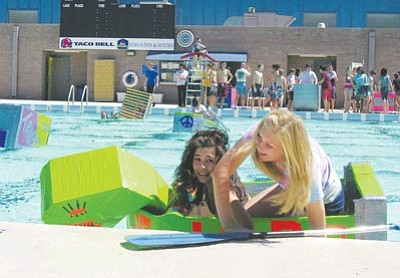 "JAMES CHILTON/Miner<br /><br /><!-- 1upcrlf2 -->/ Kingman Academy Middle School  eighth-graders Jessica Valandingham and Hanna Olney reach the far end of Centennial Pool in their monstrous green cardboard boat, ""Dino."" Their team, which included fellow eighth-grader Bryce Todriff, won Thursday's 12th Annual Cardboard Boat Races."