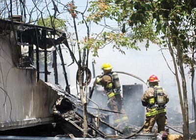 SUZANNE ADAMS/Miner<br /><br /><!-- 1upcrlf2 -->Firefighters work to smother the remaining hot spots at a mobile home fire Friday afternoon in the 500 block of Berk Avenue.