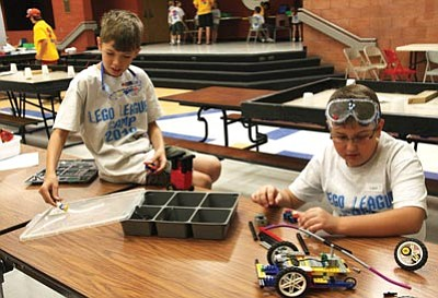 JC AMBERLYN/Miner<br /><br /><!-- 1upcrlf2 -->Andrew Nichols (left) and Logan Steffensen work on robots Friday during Lego Camp. The first session wrapped up Friday at Kingman High School. A second camp, for grades 5-8, beings July 28.