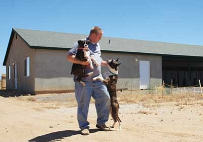 JC AMBERLYN/Miner<br /><br /><!-- 1upcrlf2 --><br /><br /><!-- 1upcrlf2 -->Jason Barnes stands with two of the family's boxers, Champion Lady Lola of Janay and her pup Pants, in front of the kennel the Barnes built for their dogs.