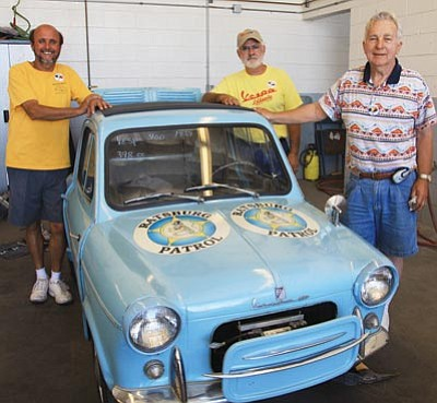 """JC AMBERLYN/Miner -- From left to right, Ronnie Dalton, Larry Newberry and John Cox stand beside a Vespa 400 1959 """"micro car"""" Tuesday at the Martin Swanty Chrysler Dodge Jeep dealership."""