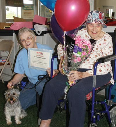 JC AMBERLYN/Miner -- Virginia Talhoun, 97 years old (right), sits with her daughter Penelope and her dog, Inky, on Tuesday as she celebrates graduation day of a dog training class she participated in at Petco