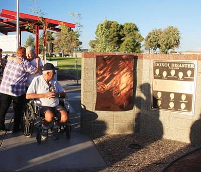 JC AMBERLYN/Miner -- George Henry looks at the new Kingman Firefighter Memorial Park structure Saturday as his wife Margaret (right) and Pam Henry hug.