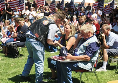 JC AMBERLYN/Miner -- Patriot Guard Rider Stephen Casey (left) presents a flag to Sharon K. and Glenn Wood Saturday during a ceremony honoring their son, fallen soldier Justin McNeley.