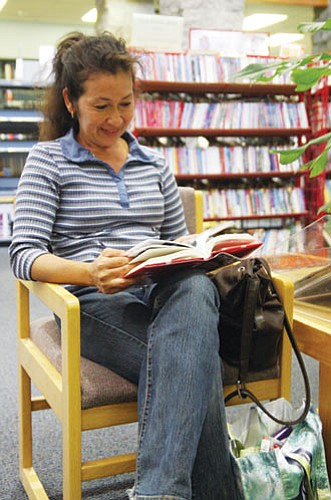 JC AMBERLYN/Miner -- Rosa Jimenez reads a book at the Mohave County Library-Kingman Saturday.<br /><br /><!-- 1upcrlf2 --><br /><br /><!-- 1upcrlf2 -->