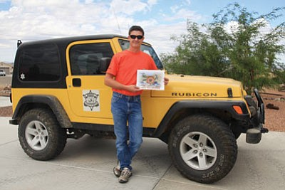 JC AMBERLYN/Miner -- Jarod Marks stands next to Luis Vega's Jeep Rubicon on Tuesday as he holds the Mohave County Search and Rescue 2011 calendar. He is a member of the all-volunteer MCSR.<br /><br /><!-- 1upcrlf2 --><br /><br /><!-- 1upcrlf2 -->