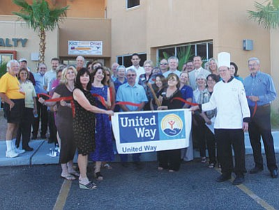 JC AMBERLYN/Miner -- Kathy Hopper cuts the ribbon as United Way and Kingman community and business members look on at the MSB building on Hualapai Mountain Road.