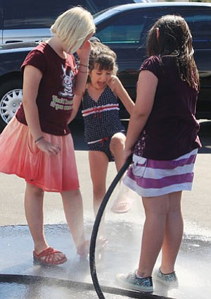 JC AMBERLYN/Miner -- From left to right, Kayley Johnston, Hailey Bata and Sophie Graham cool off during a hot summer day Saturday at Kingman Auto Plaza during a car wash to benefit St. Jude's Children's Hospital.
