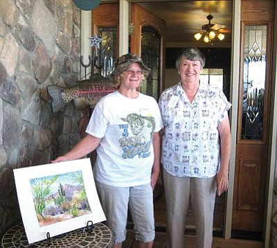 Courtesy<br /><br /><!-- 1upcrlf2 -->Kingman Area School Retirees Association member Tommie Upton stands next to an original watercolor painting by member Carol Rose. Carol donated her painting as a raffle prize to help fund KASRA's scholarship/mini-grant program. The painting was first won by member Diana Rabai (far right) who then presented it to Tommie so that it will be seen by visitors who stay at Upton's Hidden Pines Bed and Breakfast.