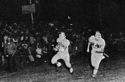 Courtesy<br /><br /><!-- 1upcrlf2 -->Dick Grounds runs in front of a standing-room-only crowd at the old football field for the 1960 Kingman Bulldogs as Carlos Lucero runs interference.<br /><br /><!-- 1upcrlf2 -->