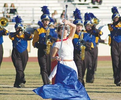 HARRY SCHUEREN/Courtesy<br /><br /><!-- 1upcrlf2 -->Kingman High School marching band color guard member Nicole Elliott performs her visual representation of the band's music as they play behind her at the Arizona Band and Orchestra Directors Association's State Championship at Phoenix College Nov. 13.<br /><br /><!-- 1upcrlf2 --><br /><br /><!-- 1upcrlf2 -->
