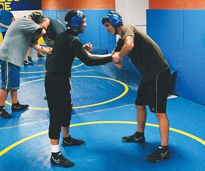 SHAWN BYRNE/Miner<br /><br /><!-- 1upcrlf2 -->Kingman High wrestlers Thomas Canez, left, and Jacob Aviles work during a hand-control drill Tuesday at KHS. The Bulldogs open the season Wednesday in Goodyear.<br /><br /><!-- 1upcrlf2 --><br /><br /><!-- 1upcrlf2 -->