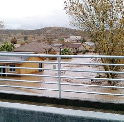 Mohave County/Courtesy<br /><br /><!-- 1upcrlf2 -->Floodwaters rise to the rooftops in the Littlefield area as Beaver Dam Wash floods Tuesday. Four homes were swept away. No deaths have been reported, but the county has declared a state of emergency.
