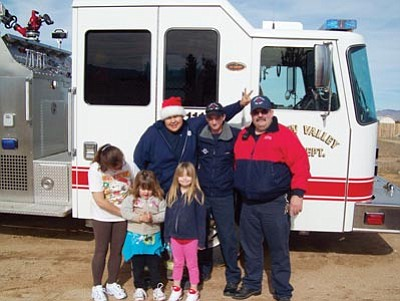 Courtesy<br /><br /><!-- 1upcrlf2 -->Golden Valley Firefighters Longfeather Fox, Luke Weber and Capt. Dave Martin pose with Diane Swaim and sisters Krissy and Katelynn Voltz in front of Santa's fire sleigh Christmas morning.