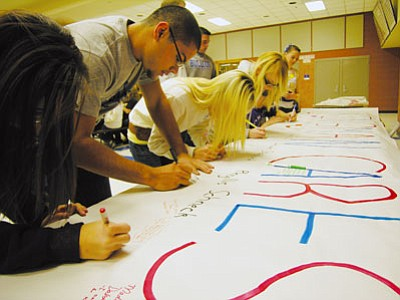 JAMES CHILTON/Miner<br /><br /><!-- 1upcrlf2 -->Students at Kingman High School write messages of condolence on a banner that will be sent to the state Capitol in honor of the six victims who died as a result of the mass shooting in Tucson Jan. 8. The banner, along with another addressed to Rep. Gabrielle Giffords, will be made available for the general public to sign during Tuesday's boys basketball game.