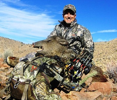 Courtesy<br /><br /><!-- 1upcrlf2 -->Local archer Jon Yokely shows the javelina he bagged with a bow during a recent hunt east of Kingman.