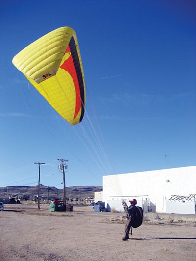 SUZANNE ADAMS/ Miner<br /><br /><!-- 1upcrlf2 -->Kingman resident Stacy Whitmore demonstrates how to inflate a paragliding wing Tuesday afternoon. Whitmore is the paraglider that Kingman residents have seen soaring around Radar Hill.