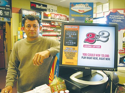 JAMES CHILTON/Miner<br /><br /><!-- 1upcrlf2 -->Hetal Dave, owner of the Gas Plus station at 2266 Kingman Ave., stands behind the counter alongside his lottery vending machine Wednesday afternoon.