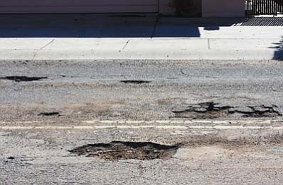 JC AMBERLYN/Miner<br> These potholes, photographed Tuesday, provide a hazard for drivers on Kino Avenue near Roosevelt Street. Road maintenance could be in trouble without new revenue.