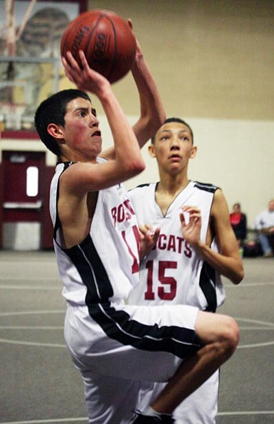 JC AMBERLYN/Miner<br> Trey Honga puts up a shot for Kingman Middle School Feb. 26 during the 2011 8th-grade boys basketball tournament held at KMS. Teammate Josh Mease watches. Lake Havasu Thunderbolt won the championship, beating KAOL 58-54 in overtime.