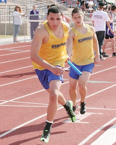DAVID BELL/Today's News-Herald<br> Kingman High's Steven Bonfield hands off to Danny Gonzalez during the 4x800 relay Saturday in Havasu. Along with teammates David Haun and Preston Hammond, the Bulldogs finished second in the race.
