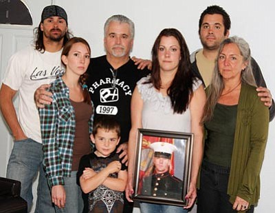 JC AMBERLYN/Miner<br> The family of Jordan Maynard, the Kingman Marine injured in Afghanistan Tuesday, is pictured Saturday in Kingman standing with a photo of him. From left to right are his brother, Levi Maynard, his sister Chelsea Curry, his father Kevin, his son Jay, his wife Jennifer, his brother Nathan and his mother Angela Patterson.