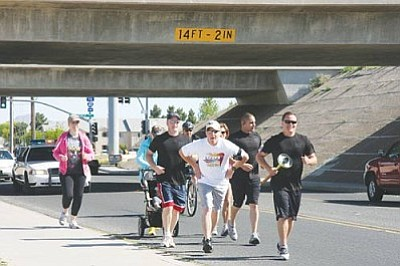 Courtesy<br /><br /><!-- 1upcrlf2 -->From left, Det. Todd Foster, Officer Adam Parrott, Det. Brian Zach and Det. Gabe Otero run through Kingman during the 2011 Law Enforcement Torch Run for Special Olympics Monday.