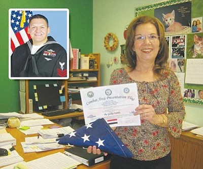 "ERIN TAYLOR/Miner<br /><br /><!-- 1upcrlf2 -->Joylene Gaska stands in her classroom with the American flag flown over Iraq in her honor by a former student. Joseph Dronchi (inset) in his ""Sailor of the Year"" photo earlier this year."
