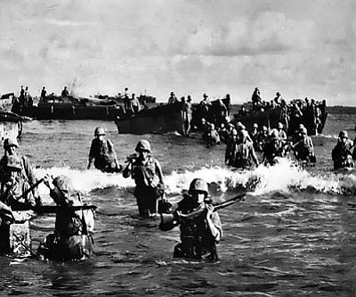 Image: Wikimedia Commons<br /><br /><!-- 1upcrlf2 -->U.S. Marines wading ashore during the WWII Battle of Tinian.<br /><br /><!-- 1upcrlf2 -->