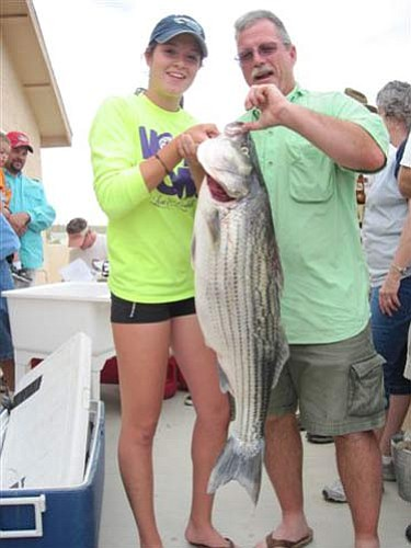 DON MARTIN/For the Miner<br /><br /><!-- 1upcrlf2 -->Natalie Casson and her uncle, Bob, show the giant striper she caught during the annual firefighters' tournament at South Cove on Lake Mead. The striper weighed 23.5 pounds.