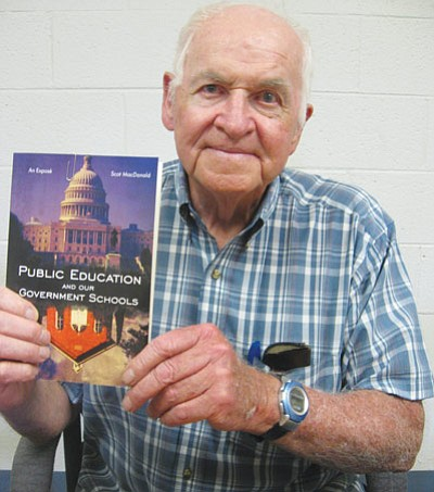 "AHRON SHERMAN/Miner<br> Scot MacDonald holds up ""Public Education and our Government Schools – an Expose,"" a book he wrote that is set for official release on July 19."