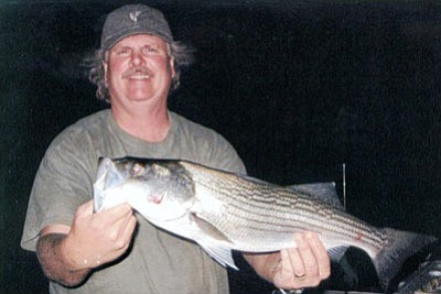DON MARTIN/For the Miner<br /><br /><!-- 1upcrlf2 -->Jim Rich, an instructor for the Hunter Education team in Kingman, shows the 4 pound, 6 ounce striper he caught Friday night on Lake Mead.