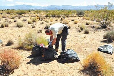 "BUTCH MERIWETHER/Courtesy<br /><br /><!-- 1upcrlf2 -->Mohave County ERACE Investigator Kevin Hartmann searches through one of 14 bags of trash haphazardly tossed out in Golden Valley to find evidence of who illegally dumped the them onto a vacant lot. Much of Hartmann's time is spent in the field searching for individuals who have been illegally dumping garbage, commonly referred to as ""wildcat dumping."" If evidence can be found determining the culprit who illegally dumped trash, several things can happen. The investigator can: visit the person's residence, give them a warning and make them clean up the illegal dump area; issue them a citation; and/or turn it over to the Mohave County District Attorney for prosecution."