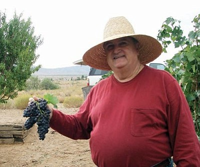 CELLA WINES/Courtesy<br /><br /><!-- 1upcrlf2 -->Carlos Cella with a bunch of his first harvest of wine grapes. Cella purchased property in Valle Vista and started growing wine grapes a few years ago. The vines finally matured this year and were harvested for Cella Wine's first bottles earlier this month.