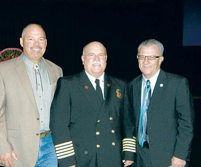 Courtesy<br /><br /><!-- 1upcrlf2 -->From left, Kingman Mayor John Salem, Arizona Fire Service Hall of Fame and Kingman Fire Chief Chuck Osterman and City Manager Jack Kramer pose after Osterman was honored.
