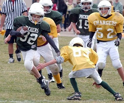 RODNEY HAAS / Miner <br /><br /><!-- 1upcrlf2 -->Packers' Derrick Kelly (32) tries to avoid a tackle by Chargers' Daniel McWilliams during the Packers' 32-20 win Saturday in the Kingman Yough Football League's semi-finals at Kingman Middle School.