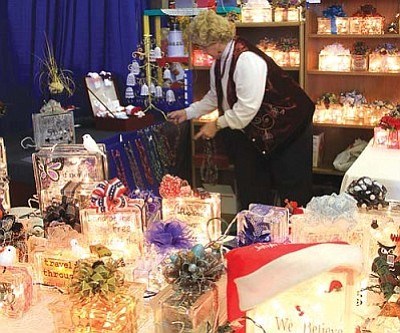 "JC AMBERLYN/Miner<br /><br /><!-- 1upcrlf2 -->Vendors at the Kingman Cancer Care Unit's 36th annual Arts and Crafts Fair sold a variety of arts, crafts, foods, and other gifts just in time for the holidays. The event helped raise funds to support the non-profit, 100-percent volunteer organization that assists local residents diagnosed with cancer. This includes help with travel, medication, housing and other expenses. In 2011, the KCCU assisted over 94 adults and children. Here, Carole Gallagher sets up a display Saturday morning for her business, ""Lady Carole's Glass Block Nightlights and Crocheted Necklaces.""<br /><br /><!-- 1upcrlf2 -->"