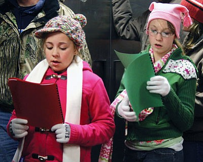 "JC AMBERLYN/Miner<br /><br /><!-- 1upcrlf2 -->The ""Santa's Hualapai Wonderland"" event at Hualapai Mountain Park drew a very large number of people last year. Here, Jazmyn Dunshie (left) and Suzzonna Sadler practice Christmas Carols as they wait in line for marshmallows at a cabin in the park."