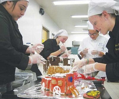 ERIN TAYLOR/Miner<br /><br /><!-- 1upcrlf2 -->Pictured from left to right are students Adriana Perez, Kelsey Jones, Carla-Selena Moreno and Emma Bumbullis putting the finishing touches on a gingerbread train and gingerbread houses.<br /><br /><!-- 1upcrlf2 --><br /><br /><!-- 1upcrlf2 -->