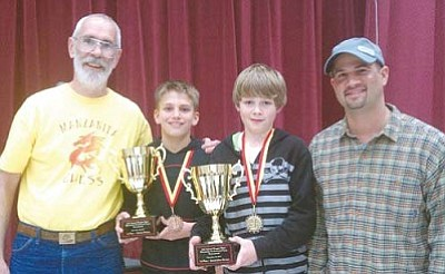 Courtesy<br /><br /><!-- 1upcrlf2 -->From left Rob Findlay, coach of intermediate players at Manzanita Elementary, Manzanita chess players Cameron Ott (third place), Alec Rose (first place) and Chad Baitinger, the primary coach at Manzanita Elementary. Ott and Rose are holding the two first-place trophies won by Manzanita's primary and intermediate teams.<br /><br /><!-- 1upcrlf2 --><br /><br /><!-- 1upcrlf2 -->