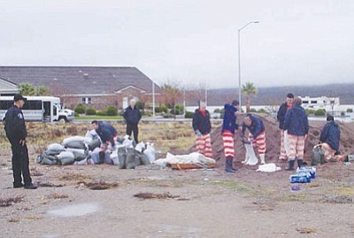 Mohave County Sheriff's Office/Courtesy<br> Jail inmates fill sandbags as part of community service work.