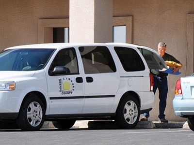 Butch Meriwether/Courtesy<br> An employee of the Mohave County Library unloads books from a van in front of the Library Annex office on Gordon Avenue.